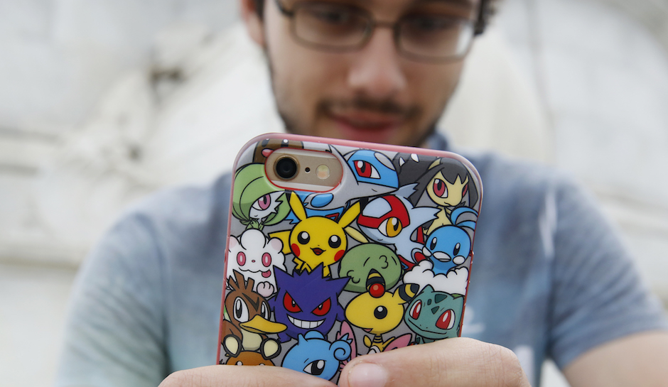A man holds a phone with Pokemon branding on its case
