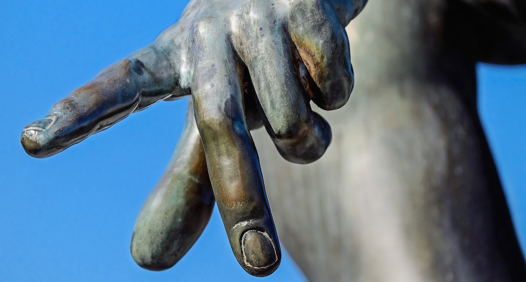 Extended index finger of a statue