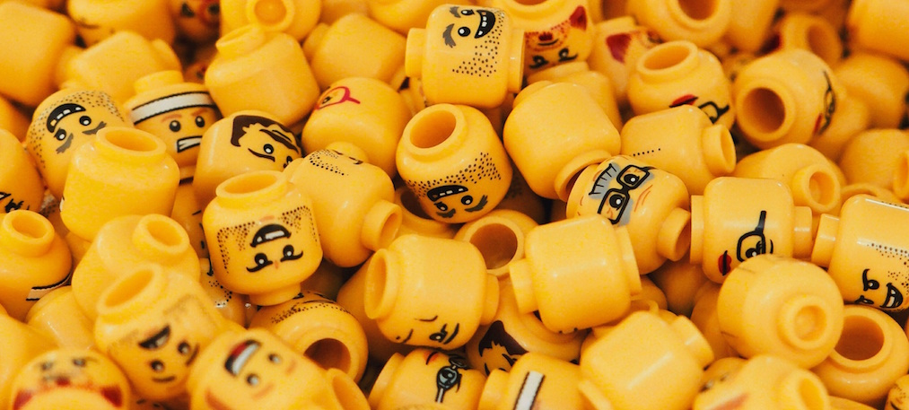 A pile of lego heads with different emotions and expressions