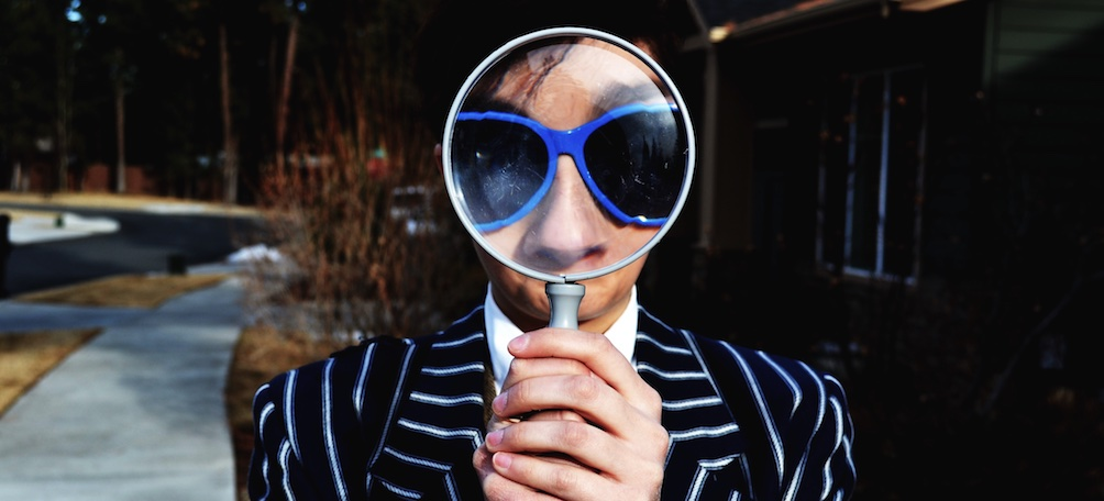 Person holding magnifying glass up to face