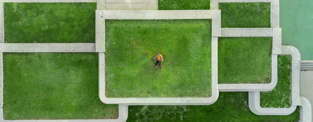 Man laying in a set of concentric grass fields