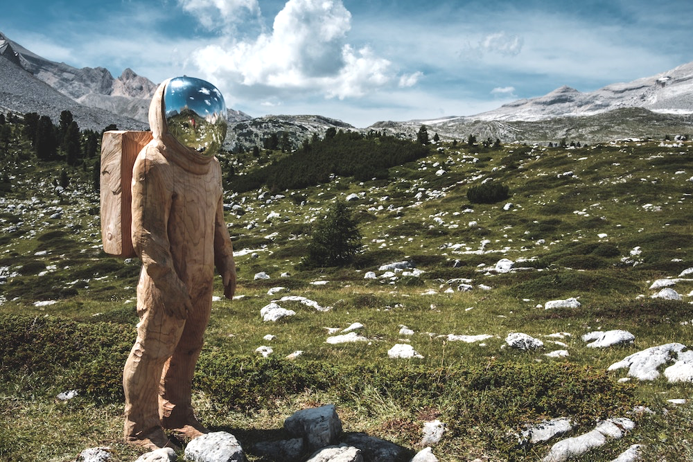 A wooden astronaut standing in the Alps