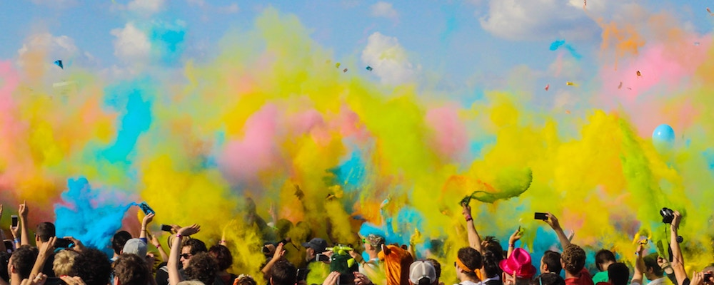 Revelers throw clouds of colored powder into the air