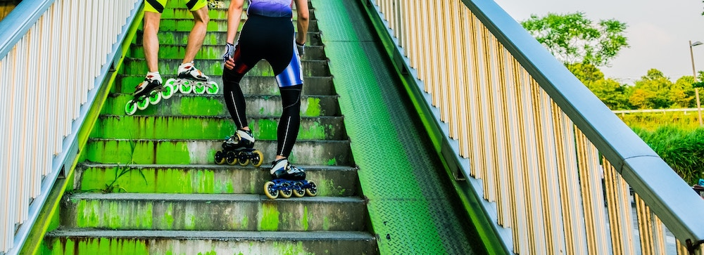 Two roller bladers tramp up a metal staircase