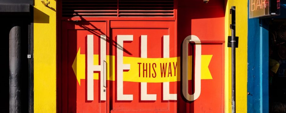 "Painted wall sign reading ""Hello"" and ""This way"""