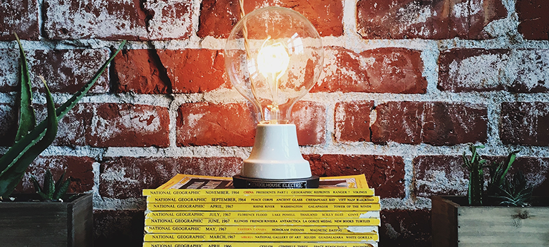 A lightbulb on a stack of Nat Geo magazines