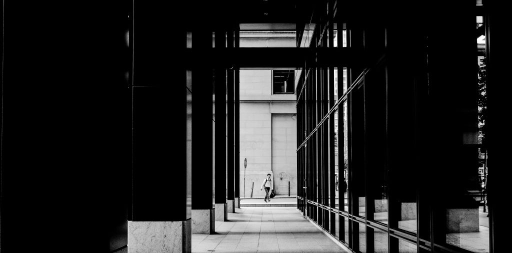 An artful photograph of a man at the end of a long, prison-like hallways of a corporate building
